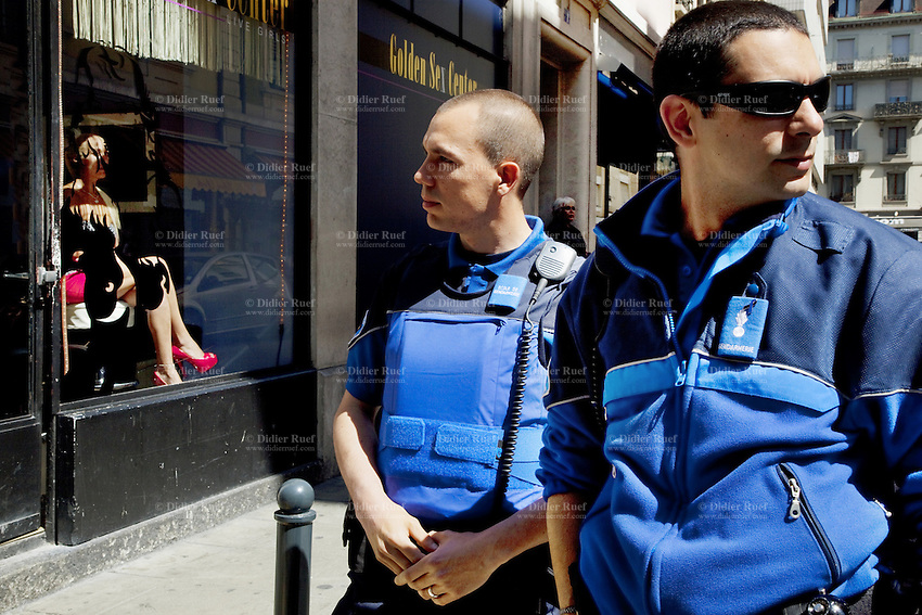 """Switzerland. Geneva. Pedestrian patrol. Two police officers walk at daytime on the streets of the Paquis neighborhood, known for its Red-light district. Street prostitution. Most of the prostitutes work in the streets. Others wait inside seated  and look through the windows for customers. Prostitution is often referred to as """"the world's oldest profession"""". Both policemen are wearing a ballistic vest, bulletproof vest or bullet-resistant vest which is an item of personal armor that helps absorb the impact from knives, firearm-fired projectiles and shrapnel from explosions, and is worn on the torso. Soft vests are made from many layers of woven or laminated fibers and can be capable of protecting the wearer from small-caliber handgun and shotgun projectiles. Both policemen have also a two-way radio which is a radio that can both transmit and receive (a transceiver). A two-way radio (transceiver) allows the operator to have a conversation with other similar radios operating on the same radio frequency (channel). Two-way radios are available with hand-held portable configurations. Hand-held radios are often called walkie-talkies or handie-talkies. 14.05.12 © 2012 Didier Ruef"""
