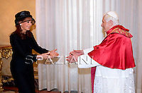 Argentine President Cristina Fernandez de Kirchnerat (L) exchange gifts with Pope Benedict XVI (C) during their private audience at the Vatican on November 28, 2009.