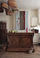 In the kitchen an antique shop counter serves as a sideboard while added storage, for fruit and vegetables from the garden, comes from baskets hanging from the tongue-and-groove ceiling