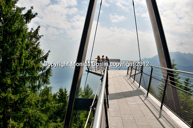 Three women stand at the end of an observation deck at Cardada (elevation of 1,340 meters or 4,400 feet) on Cimetta mountain in the Lepontine Alps above Locarno on Lake Maggiore.