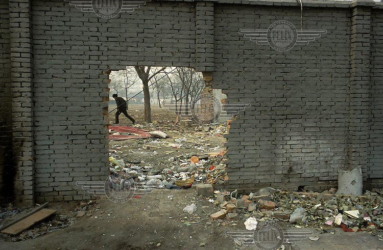 "A wall is knocked down to make way for the 2008 Beijing Olympic Games. This site is the exact spot where the ""Bird's nest"" National Stadium now stands."