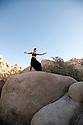 Woman practicing taichi in a bolder landscape.