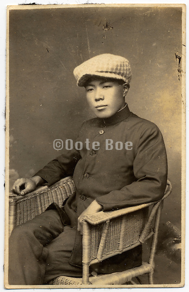Studio portrait of an Asian man in Western style clothing.
