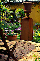 A rusted steel garden urn stands tall on pedestals in a small courtyard garden against an chalky ochre painted walls