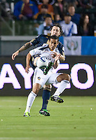 CARSON, CA – April 2, 2011: LA Galaxy forward Miguel Lopez (25) tries to shield Philadelphia Union defender Danny Califf (4) from the ball during the match between LA Galaxy and Philadelphia Union at the Home Depot Center, March 26, 2011 in Carson, California. Final score LA Galaxy 1, Philadelphia Union 0.