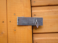 Lock on a shed door held shut with a bent nail.