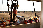 Two Southern Sudan workers run an oil rig next to a small village of displaced people near the town of Melut runs an oil rig in Upper Nile State, Southern Sudan's most productive oil area.
