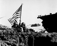 First flag on Guam on boat hook mast.  Two U.S. officers plant the American flag on Guam eight minutes after U.S. Marines and Army assault troops landed on the Central Pacific island on July 20, 1944. Batts. (Marine Corps)<br /> NARA FILE #:  127-N-88073<br /> WAR &amp; CONFLICT BOOK #:  1177