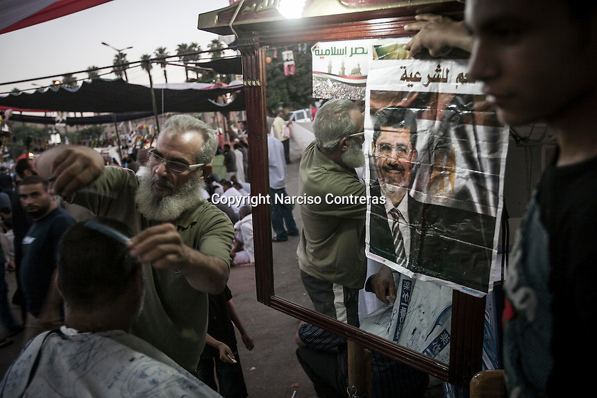 In this Thursday, Aug. 08, 2013 photo, a supporter of the ousted president Mohammed Morsi gets a brand new hearcut dress in a street barbershopchild at the sit-in of the Cairo University in Giza district. (Photo/Narciso Contreras).