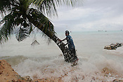 Pita Meanke, of Betio village, stands beside a tree as he watches the 'king tides' crash through his families sea wall, and the sea spills onto his family property, on the South Pacific island of Kiribati.