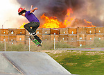 Brett Gomez attempts to land a trick as a large fire burns at the Yuma Mesa Fruit Growers Association, located at 2240 S. Pacific Ave just East of the Kennedy Skate Park Friday evening. A stack of cardboard and wooden crates stored at the business went up in flames sending a large plume of black smoke into the air that could be seen throughout the city.