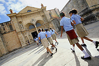"Dominican Republic. Distrito Nacional Province. Santo Domingo. Schoolgirls, wearing their uniforms - a blue shirt and a beige skirt - walk towards the entrance of the  oldest church on the island, the cathedral "" Catedral Primada de América"". © 2006 Didier Ruef"