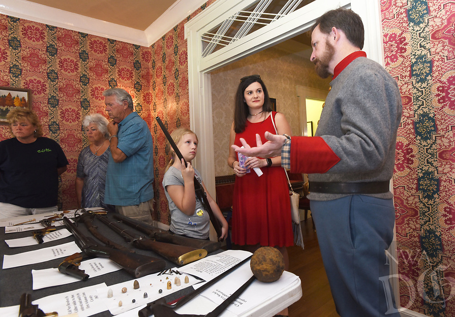 NWA Democrat-Gazette/FLIP PUTTHOFF <br /> BATTLE OF FAYETTEVILLE REMEMBERED<br /> Eleanor Gray, 9, and her mentor, Jordan Garrett (center) learn Saturday April 15 2017 about rifles used in The Battle of Fayetteville from Civil War actor Jim Spillars during a program commemorating The Battle of Fayetteville. Events at Headquarters House on East Dickson Street included artifact displays, Civil War era music and dance, cannon drills and a commemoration ceremony. The Battle of Fayetteville was fought April 18, 1863. Headquarters House served as a headquarters of Union and Confederate troops at different times during the Civil War.