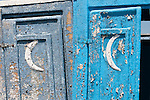 Weathered blue outhouse doors with crescent moon on the doors.