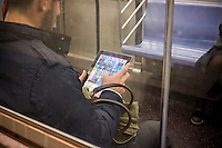 A subway rider plays the popular mobile game Candy Crush Saga on his iPad in New York on Friday, april 259, 2014.  The game accounts for almost 80 percent of King Digital Entertainment's revenue, achieving that from sales of add-ons and upgrades to the free game.  (© Richard B. Levine)