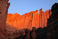 isher Towers, near Moab, Utah, is a scarp of cliff walls, spires, and rock pedestals that rises up above the Colorado River forming castle-like towers and deep cathedrals. ..As with most areas of the Colorado Plateau, this is a story of erosion. First, starting about 320 million years ago (mya) during the Permian and continuing for more than 70 million years into the Triassic, rivers and streams carved up the Umcompahgre Highlands to the east depositing first cobbles and pebbles of granite, quartz, schist, mica, feldspar, and quartzite mixed with sand and mud followed by just fine grained sand and sediment into the region. ..Then, for the next 160-170 million years, these layers of sand and mud and rock conglomerates were buried under still more sand and mud and other sedimentary rock layers until the Colorado Plateau began to uplift between 80 and 50 mya. This uplift began the cycle of erosion again for millions of years more until today the Triassic Moenkopi Formation stands like towers in the desert on a base of Permian Cutler Formation... all exposed into a fantasyland formation by the erosive power of water and wind.