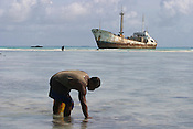 Kamatie Kainti-Kuaba, of Betio village, looks for and collects shell fish for his family to eat on Red Beach (so called because of the amount of American soldiers who  lost their lives and spilled their blood,in a fierce battle with the Japanese occupiers of the island in WW2), on the island of Kiribati in the South Pacific. The islands, and their way of life, are endangered by rising sea water levels which are eroding the fragile atoll, home to approximately 92,000 people.