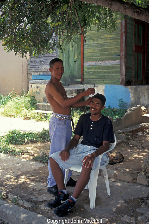 Young man getting an outdoor haircut in the town of Barahona, Dominican Republic