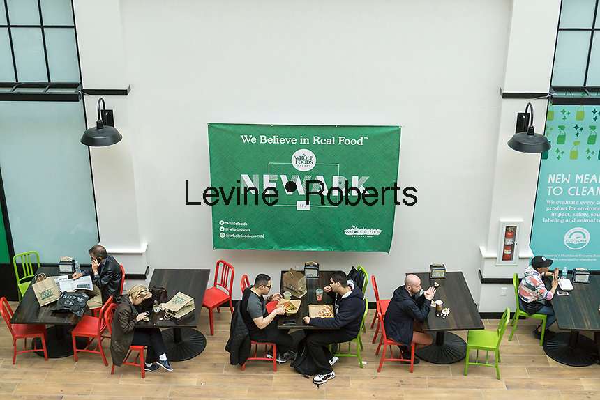 Shopper eat their take-out foods in the new Whole Foods Market in Newark, NJ on opening day Wednesday, March 1, 2017. The store is the chain's 17th store to open in New Jersey. The 29,000 square foot store located in the redeveloped former Hahne & Co. department store building is seen as a harbinger of the revitalization of Newark which never fully recovered from the riots in the 1960's.  (© Richard B. Levine)