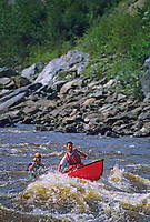 Canoers paddle through canyon rapids on the Forty Mile River which flows from Alaska through Canada and back to Alaska, joining the Yukon River.