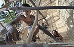 Mip Mach builds a rice bank storage structure in the Cambodian village of Char. The structure is part of a program sponsored by the Community Health and Agricultural Development program of the Methodist Mission in Cambodia. Yee Nann (below) helps him.