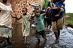 DUBIE, DEMOCRATIC REPUBLIC OF CONGO DECEMBER 5: Refugees cross a river on December 5, 2005 in Dubie, Katanga Province in Congo, DRC. They have been fleeing fighting between the Congolese army and Mai-Mai rebels in Eastern Congo, and thousands of them arrived in Dubie in December 2005. They are some of the victims of the civil war that started in 1996. Many people have moved from area to area the last years trying to find safety. About four million people have died in Congo since 1996, making it the deadliest humanitarian crisis in recent memory. Most of people have died of preventable diseases such as malaria, measles, diarrhea, respiratory infections and malnutrition. The health system has collapsed and very few people have access to healthcare. Congo is planning to hold general elections by June 2006, the first democratic elections in forty years. (Photo by Per-Anders Pettersson/Getty Images)