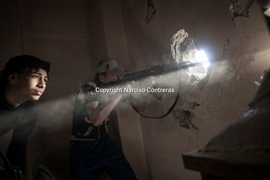 Rebel fighters fire over their enemy's position as skirmishes spark out at the front line in Bustan Al Qasr frontline in Aleppo, Syria.