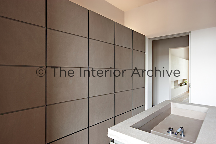 A contemporary, minimalist kitchen with a flush cupboard wall and a central island unit with a recessed sink.