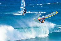 Windsurfer catches air riding surf off Hookipa Beach, Maui.