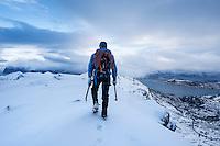 Hiker on winter summit of Hustind mountain peak, Flakstadøy, Lofoten Islands, Norway