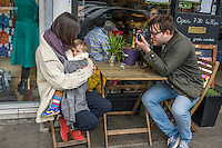 A mother breastfeeds her 15 month old boy from a sling while sitting outside a cafe.  Her partner is taking pictures of them with his camera.<br /> <br /> London, England, UK<br /> 22-03-2015<br /> <br /> &copy; Paul Carter / wdiip.co.uk