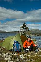 Gutt i teltåpning på øy i Rogen ---- Man in front of tent on island on lake Rogen