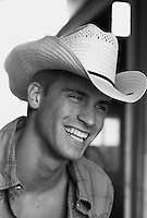 Portrait of a man smiling wearing a cowboy hat