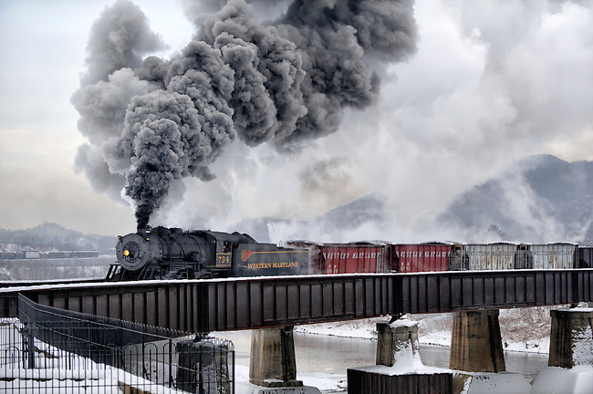 Crossing the Potomac River from the Ridgley WV yards and shops, and into the station across the river at Cumberland MD, this reenactment on the old Western Maryland was done on a fifteen degree morning. Good thing, too. We may not have a lot of sunlight under that winter overcast, but look at all the great smoke!<br /> <br /> Interestingly, you can ride this steam train too, but with a twist. It is actually a rails-with-trail because one of the double tracks was pulled up years ago. Load your bike onto the train for a ride up the mountain, and coast back down the sixteen miles through the woods back into town.<br /> <br /> This was a photographer's special and we shot all day in many locations along the sixteen miles that still operates. Click here to see the rest of the gallery:<br /> <br /> Click here for the railroad's website and see the schedule: http://www.wmsr.com/