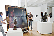 """Workers transport one of Bartolome Estaban Murillo's earliest works, """"The Blessed Jiles Before Pope Gregory The 9th,"""" through a gallery of sculptures by Auguste Rodin, including """"The Kiss,"""" inside the new 127,000-square-foot expansion to the North Carolina Museum of Art, Tues., April 6, 2010. The $75 million expansion project brings a modern look to the museum along with more than 100 new acquisitions in addition to the 5,000 pieces already in the museum's permanent collection."""