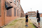 December 22, 2014. Lexington, North Carolina.<br />  Frank Callicutt does  leg lifts on the wall of the abandoned Lexington Furniture factory as Mayor Newell Clark and Chris Phelps look on.<br />   Newell Clark, the 43 year old mayor of Lexington, NC, leads a group of friends and colleagues on a 4 times a week exercise routine around downtown. The group uses existing infrastructure, such as an abandoned furniture factory, loading docks, stairs, and handrails to get fit and increase awareness of healthy lifestyles in a town more known for BBQ.<br /> Jeremy M. Lange for the Wall Street Journal<br /> Workout_Clark
