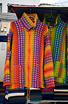 Colorful woven jackets on display in marketplace in Ecuador