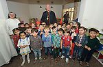 Cardinal Timothy Dolan, the archbishop of New York, poses with children displaced by war in a preschool run by the Dominican Sisters of St. Catherine of Siena in Ankawa, near Erbil, Iraq, on April 9, 2016. <br /> <br /> Dolan, chair of the Catholic Near East Welfare Association, is in Iraqi Kurdistan with other church leaders to visit with Christians and others displaced by ISIS. The Dominican Sisters were themselves displaced by ISIS, and have established schools and other ministries among the displaced.
