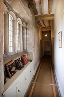 Contemporary cupboards beneath the mullioned windows in this long corridor also create a window seat