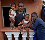 A father and three of his children in Batey Bombita, a community in the southwest of the Dominican Republic whose population is composed of Haitian immigrants and their descendents.