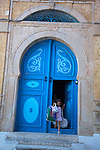 A girl steps out the front door of her house in Sidi Bou Said, a charming town in northern Tunisia of whitewashed walls and sea blue windows and doors.