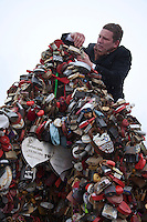 Moscow, Russia, 14/02/2011..A bridegroom climbs on top of an artificial tree to hang a wedding padlock in temperatures of minus 14C.
