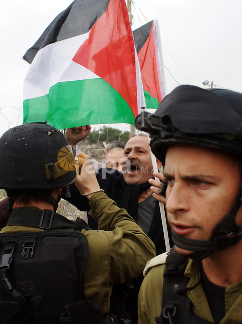 A Palestinian demonstrator argues with an Israeli soldier during a protest against Israel's controversial separation barrier organized by Palestinian and foreign peace activists in the West Bank village of Beit Omar, near Hebron, on 12 February 2011. Israel says the network of steel and concrete walls, fences and barbed wire is needed for security while the Palestinians view it as a land grab that undermines their promised state . Photo by Najeh Hashlamoun