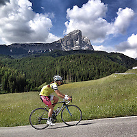 A lone cyclist ascends the precipitous slopes of Passo delle Erbe, in the heart of the Dolomites, Südtirol (South Tyrol), Italy. Also known as Würzjoch (and in Ladin as Jü de Börz) the 2003 meter high mountain pass connects the city of Brixen in the Eisacktal with San Martin de Tor in the Val Gardena.