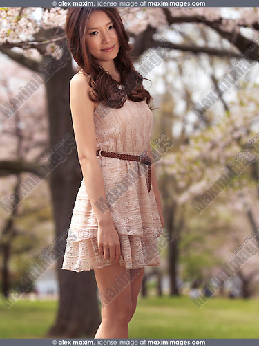 Young smiling Asian woman in a beige summer dress standing under blooming cherry trees in a park