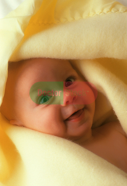 happy newborn baby wrapped comfortably in warm yellow blanket