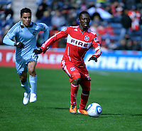 Chicago Fire midfielder Patrick Nyarko (14) dribbles down the field in front of Sporting KC midfielder Omar Bravo (99).  The Chicago Fire defeated Sporting KC 3-2 at Toyota Park in Bridgeview, IL on March 27, 2011.