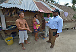 John Nduna (right), the general secretary of the ACT Alliance, talks with Rolando Estosane (left) and Mercy Estosane, who is holding her 2-year old son Jay, in Bacubac, a neighborhood in Basey in the Philippines province of Samar that was hit hard by Typhoon Haiyan in November 2013. The storm was known locally as Yolanda. Translating for them is Efrain Ancaha, the neighborhood captain. The ACT Alliance has been providing a variety of forms of assistance to survivors here, and Nduna and other ACT Alliance leaders spent several days in affected communities learning first hand about the network's emergency response and long-term plans for recovery and rehabilitation.