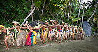 Talented traditional dancers form a  konga line in front of stone money in Yap Micronesia (Photo by Matt Considine - Images of Asia Collection)