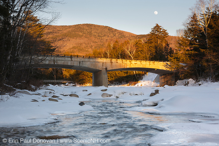 Road Bridge during the in winter months. This bridge crosses the East Branch of the Pemigewasset River in Lincoln, New Hampshire USA along Kancamagus Scenic Byway (Route 112). A suspension bridge used for foot traffic is in the background and a nearly full moon can be seen in the sky
